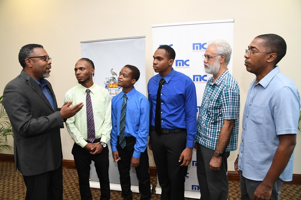 Dwayne Russell (left), general manager of MC Systems congratulates scholarship recipients, (from second left), Ashray Soares; Tevin Taylor and Shane Okukenu. Sharing in the moment are: Dr. Curtis Busby-Earle (right), programme coordinator of the UWI China Institute of Information Technology (CIIT) Bachelors of Science in Software Engineering (BSC SWEN) , Mona Campus and Professor Paul Reese, Chair, UWI-CIIT BSc SWEN Programme Oversight Committee.
