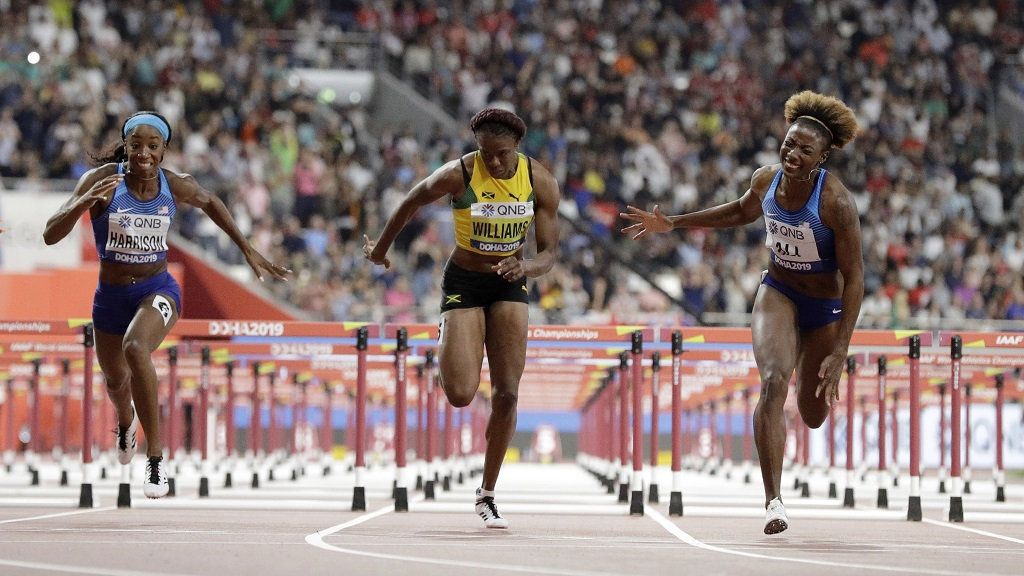 Nia Ali, of the United States, right, wins the gold medal in the women's 100m hurdles final at the World Athletics Championships in Doha, Qatar, Sunday, Oct. 6, 2019. At left is Kendra Harrison, of the United States, silver, and Danielle Williams, of Jamaica, bronze. (AP Photo/Petr David Josek).