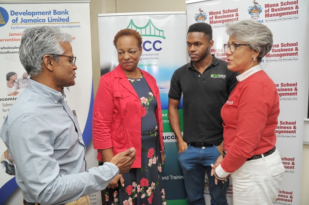 (From left) Douglas Lindo, UWIVC competition advisor, makes a point to Yekini Wallen-Bryan of Pree Labs Ltd., second place winner in the 2018 cohort of the Vincent HoSang/ UWI Venture Competition (UWIVC), Barbara Miller, marketing and public relations, Caribbean Food Delights and Kim Mair, CEO, JMMB Joan Duncan Foundation.