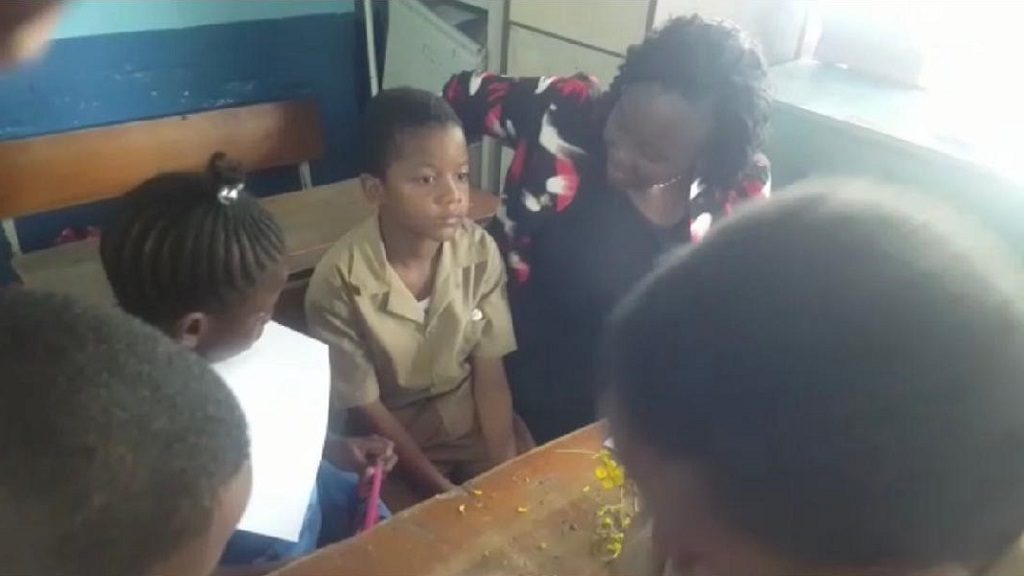 Peers and a visiting teacher around Daryl Harris on Tuesday morning amid his grief at the loss of his friend, Benjamin Bair, in a tragedy at Clan Carthy Primary School in St Andrew on Monday afternoon.