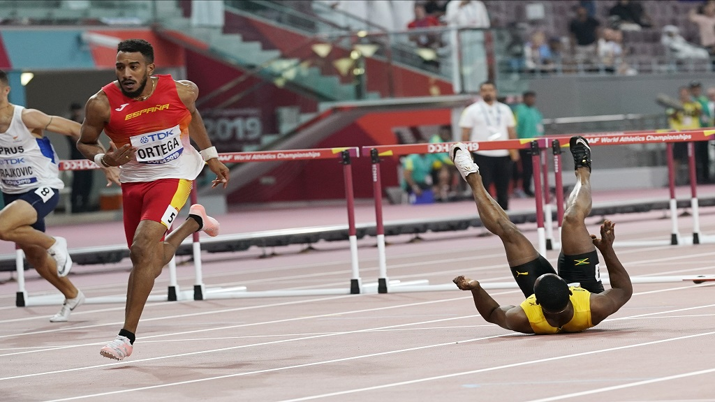 Omar Mcleod, of Jamaica, right, falls as Orlando Ortega, of Spain, finishes the the men's 110m hurdles final during the World Athletics Championships in Doha, Qatar, Wednesday, Oct. 2, 2019. (AP Photo/David J. Phillip).