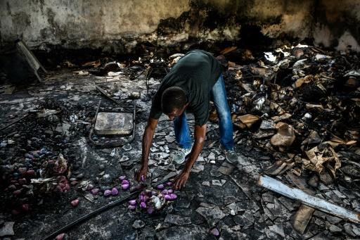 Un des employés de l'entreprise Caribbean Craft nettoie le site ravagé par un incendie, le 2 octobre 2019 à Port-au-Prince - CHANDAN KHANNA
