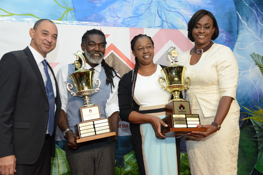 2018 Male and Female Household Workers of the Year, Michael Brown and Rosemarie Forrester beam with pride, after receiving their trophies from GraceKennedy Group CEO, Don Wehby (left) and Guest Speaker Juliet Holness, MP (right).