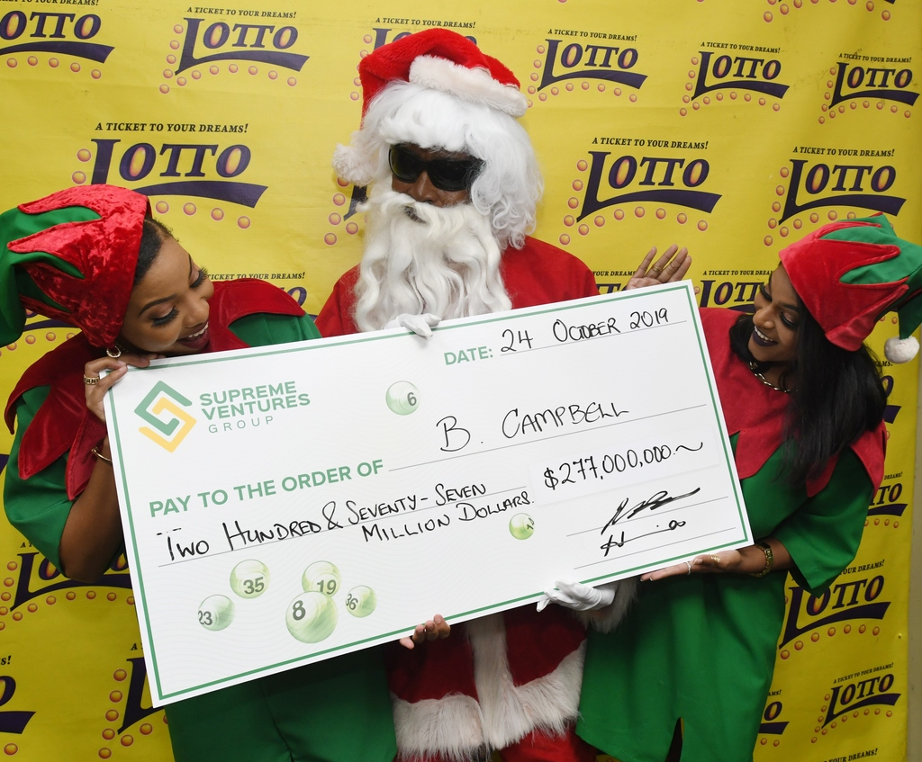 Supreme Ventures Draw Officers Peta-Gaye Sutherland (left) and Lisa McDonald (right) celebrate with $277 Million Lotto winner B. Campbell who came to collect his winnings.