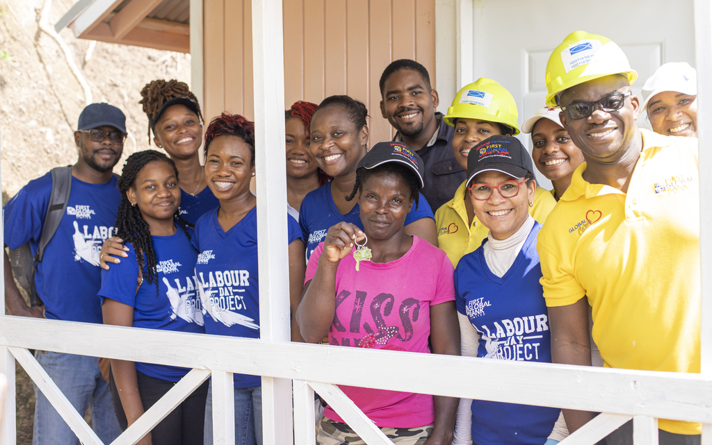 First Global Bank volunteers are all smiles after building a new home for Deniese Green.