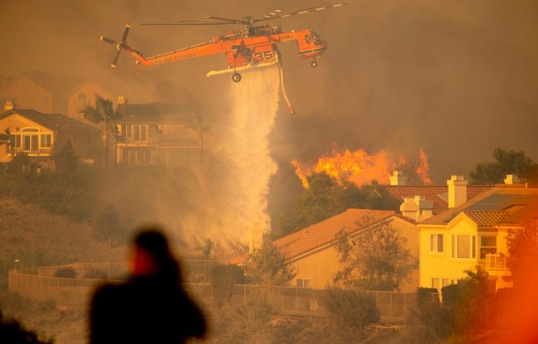 """Un hélicoptère largue de l'eau pour tenter de stopper l'incendie baptisé """"Saddleridge Fire"""" qui progresse à une vingtaine de km au nord de Los Angeles, le 11 octobre 2019"""