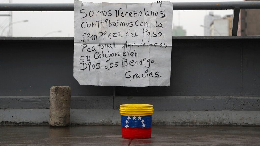 "In this October 8, 2019 photo, a sign asking for money in exchange for keeping a bridge clean hangs in Lima, Peru. The sign reads in Spanish ""We are Venezuelans. We contribute to the cleaning of this pedestrian pass. We appreciate your collaboration. May God bless you. Thank you."" (AP Photo/Martin Mejia)"