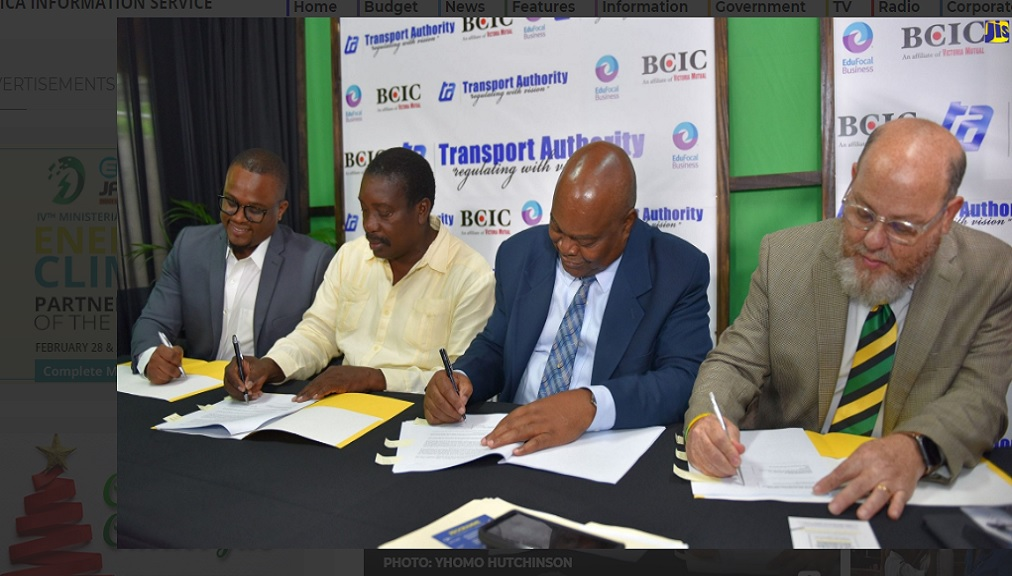 Minister of Transport and Mining, Robert Montague (second left), signs a tripartite agreement for an online training programme for Public Passenger Vehicle drivers and conductors, with (from left) Chief Executive Officer of EduFocaL Business Limited, Gordon Swaby; Managing Director of the Transport Authority, Cecil Morgan, and Managing Director of British Caribbean Insurance Company, Peter Levy. The ceremony was held at the Ministry's office in Kingston on Thursday (November 21).