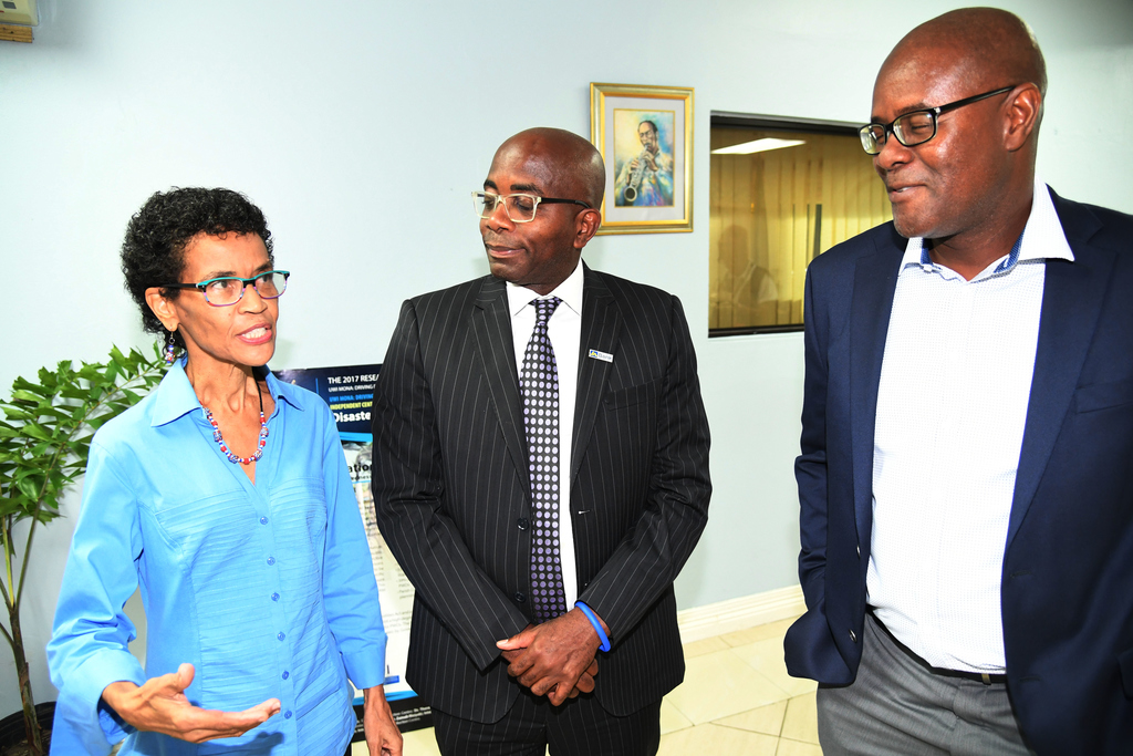 Curtis Martin (centre), Managing Director of JN Bank and Lenworth Kelly (right), President of the Incorporated Masterbuilders Association of Jamaica, listen keenly to a point being made by Dr Barbara Carby, Director of the Disaster Risk Reduction Centre at The University of the West Indies, during a recent public forum.