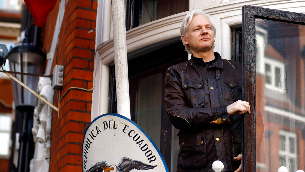 In this Friday, May 19, 2017 file photo, WikiLeaks founder Julian Assange looks out from the balcony while claiming political asylum at the Ecuadorian embassy in London. (AP Photo/Frank Augstein, File)