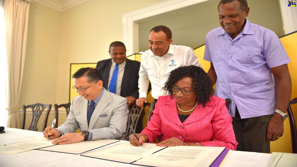 Japanese Ambassador to Jamaica, Hiromasa Yamazaki (seated left), and Principal of Tacius Golding High School, Lena Russell, sign a contact for grant funding of $15 million to buy two buses for the institution. Looking on (from left standing) are Acting Director, Safety and Security in Schools Unit, Ministry of Education, Richard Troupe; Minister of Health and Wellness and MP for West Central St Catherine, where the school is located, Dr Christopher Tufton; and School Board Chairman, Rev. Futtremann White.