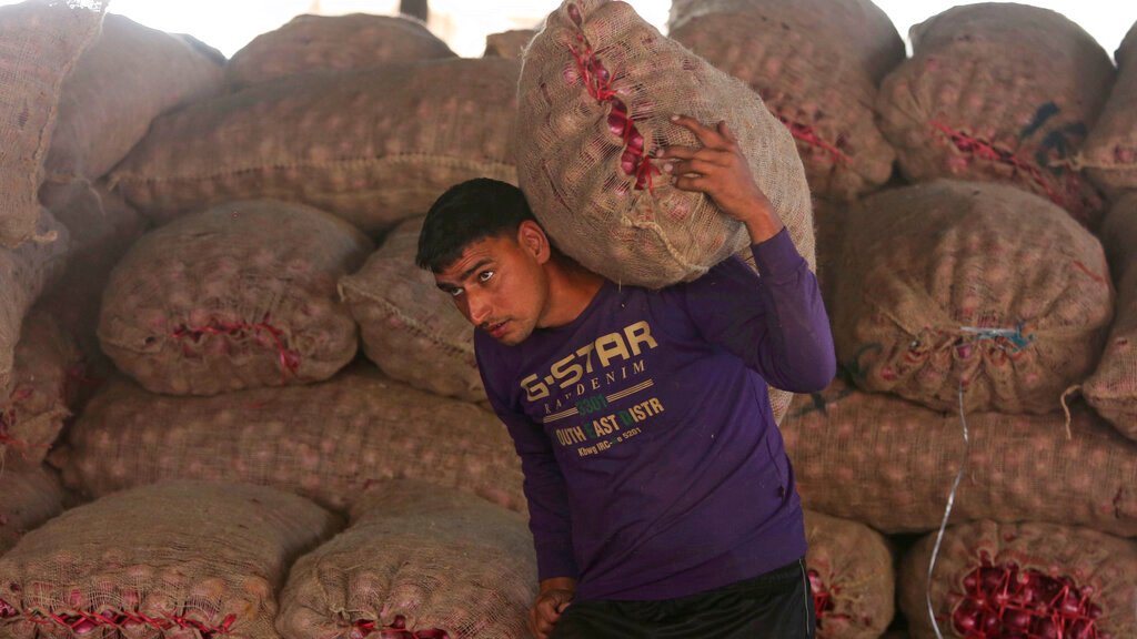 An Indian labourer carries a sack of onions at a wholesale market on the outskirts of Jammu, India, November 29, 2019. India's economic growth has slipped to 4.5%, the slowest annual pace in six years, in the July-September quarter with labor-intensive manufacturing sector registering a negative growth. (AP Photo/Channi Anand)
