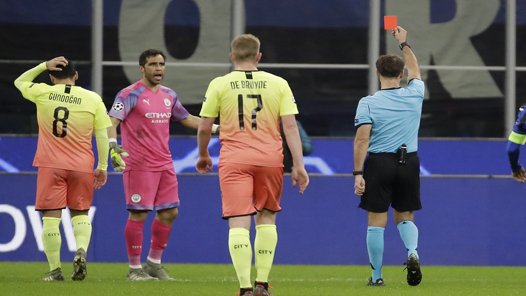 Referee Aleksei Kulbakov, right, gives a red card to Manchester City's goalkeeper Claudio Bravo, second from left, during the Champions League group C football match against Atalanta at the San Siro stadium in Milan, Italy, Wednesday, Nov. 6, 2019. (AP Photo/Luca Bruno).