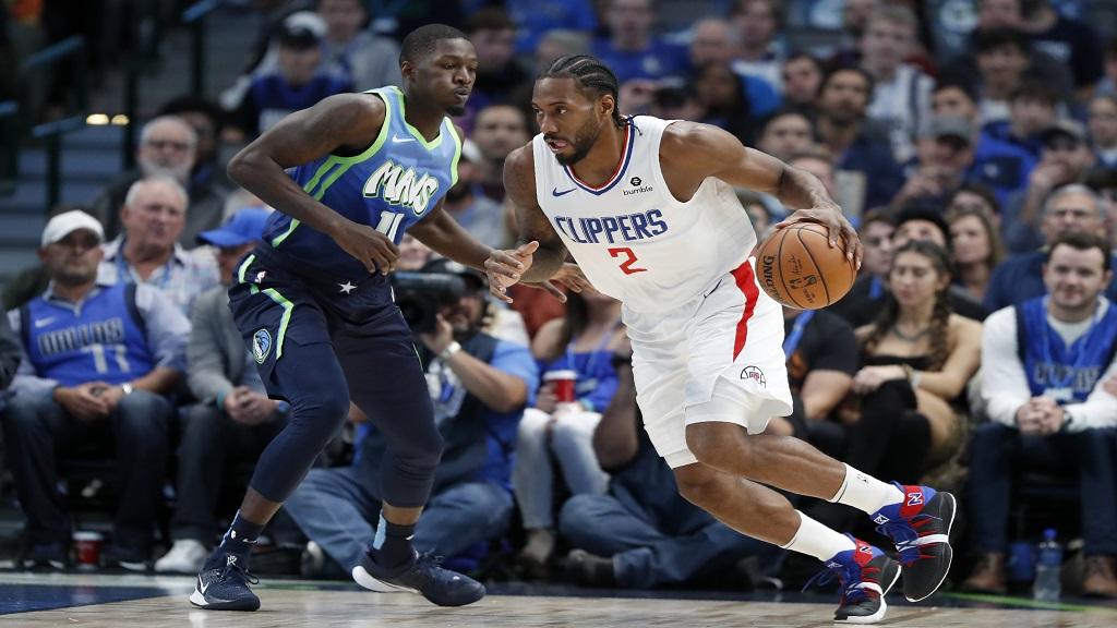 Dallas Mavericks forward Dorian Finney-Smith (10) defends as Los Angeles Clippers forward Kawhi Leonard (2) works for a shot opportunity in the first half of an NBA basketball game in Dallas, Tuesday, Nov. 26, 2019. (AP Photo/Tony Gutierrez).
