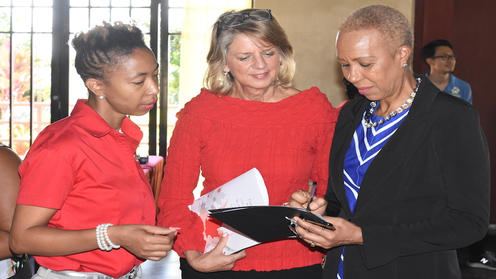 Technology Minister Fayval Williams (right); Canadian High Commissioner to Jamaica Laurie Peters (centre) CUSO representative Roberta Ellis examine the the schedule of activities at World Tech Open Day  in Kingston. (Photo: Marlon Reid)