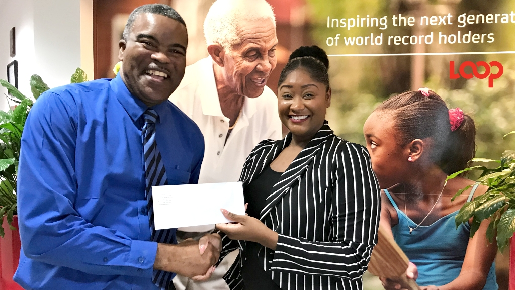 Past President of the National Domino Association, Acting Inspector Rodney Inniss accepted the cheque from Digicel Marketing Manager Risha Daniel.