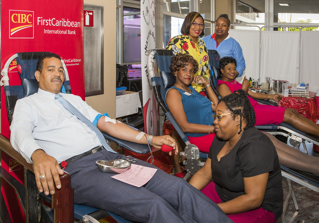 CIBC FirstCaribbean  International Bank Managing Director Nigel Holness is prepared to give blood by Nurse Tanish Walker (stooping) watched by (l-r sitting)   bank executives Rosemarie Hemmings Davis and Claudia Forbes and (standing) the Jamaica Blood Bank's Keishawna Pinnock and Esther Campbell.