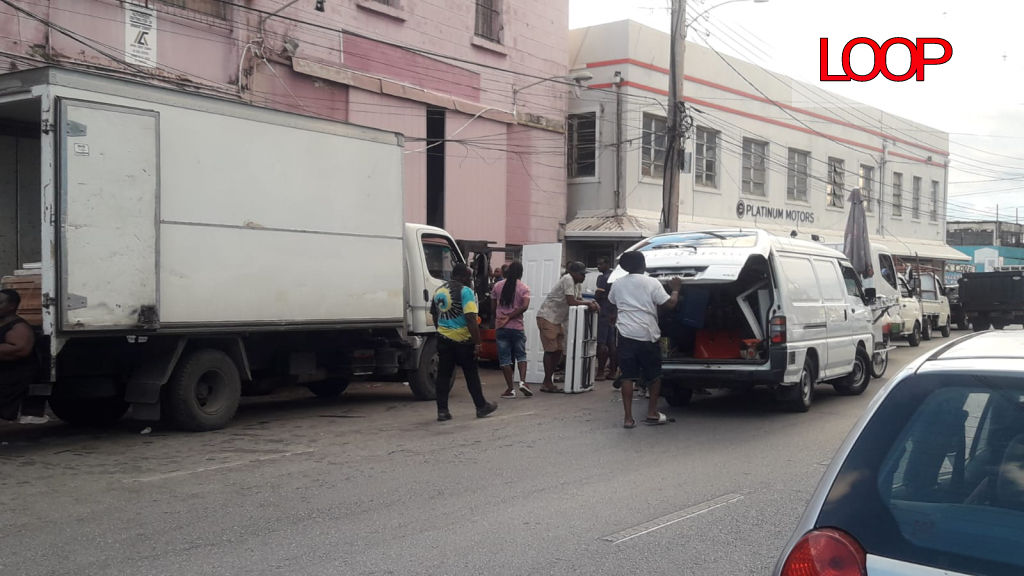 Trucks being loaded by persons on the last business day.