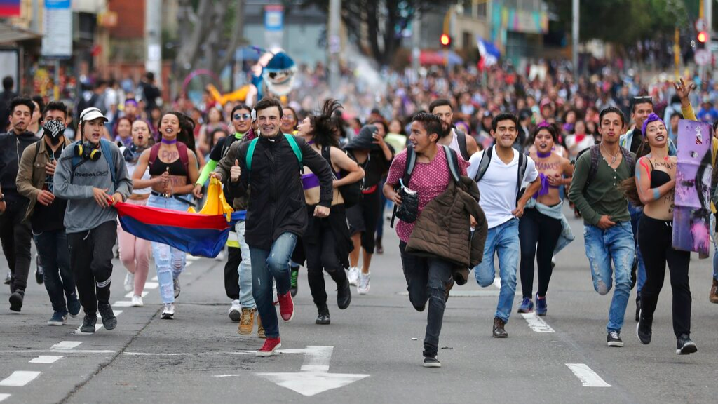 Anti-government demonstrators run during a protest in Bogota, Colombia, November 25, 2019. Authorities are maintaining a heightened police presence amidst scattered unrest in the aftermath of a mass protest that drew about 250,000 to the streets Thursday. (AP Photo/Fernando Vergara)