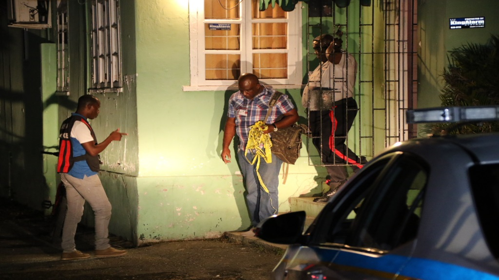 Police personnel, including investigators, at a shooting scene where a massage parlour came under gunfire in St Andrew on Saturday night.