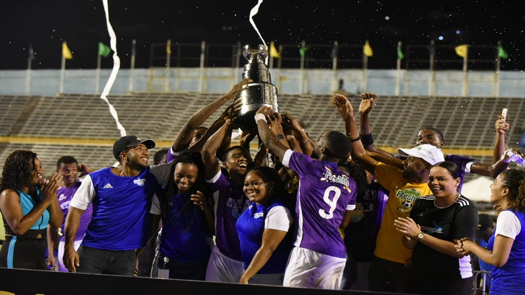 Kingston College players, officials and supporters celebrate with the all-island ISSA Champions Cup after defeating Clarendon College 1-0 in the final at the National Stadium on Saturday, November 23, 2019.  (PHOTO: Marlon Reid).