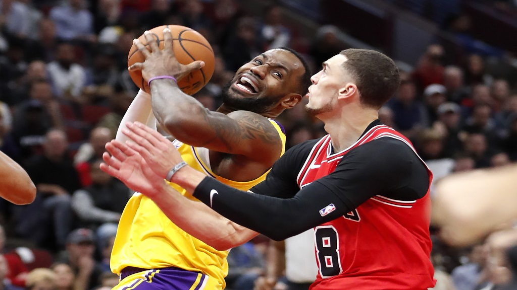 Los Angeles Lakers' LeBron James, left, drives to the basket past Chicago Bulls' Zach LaVine during the first half of an NBA basketball game Tuesday, Nov. 5, 2019, in Chicago. (AP Photo/Charles Rex Arbogast).
