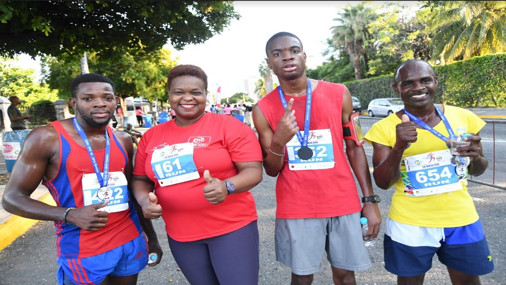 Campion College's Noel-Jonathon Ellis (3rd left), who won the recent Civil Service Week/First Heritage Co-operative (FHC) Credit Union 5K run/walk,  poses with  third-place Ricondi Salkey (left), Roxann Linton (2nd left), CEO of FHC and second-place Claude Fraser (right).
