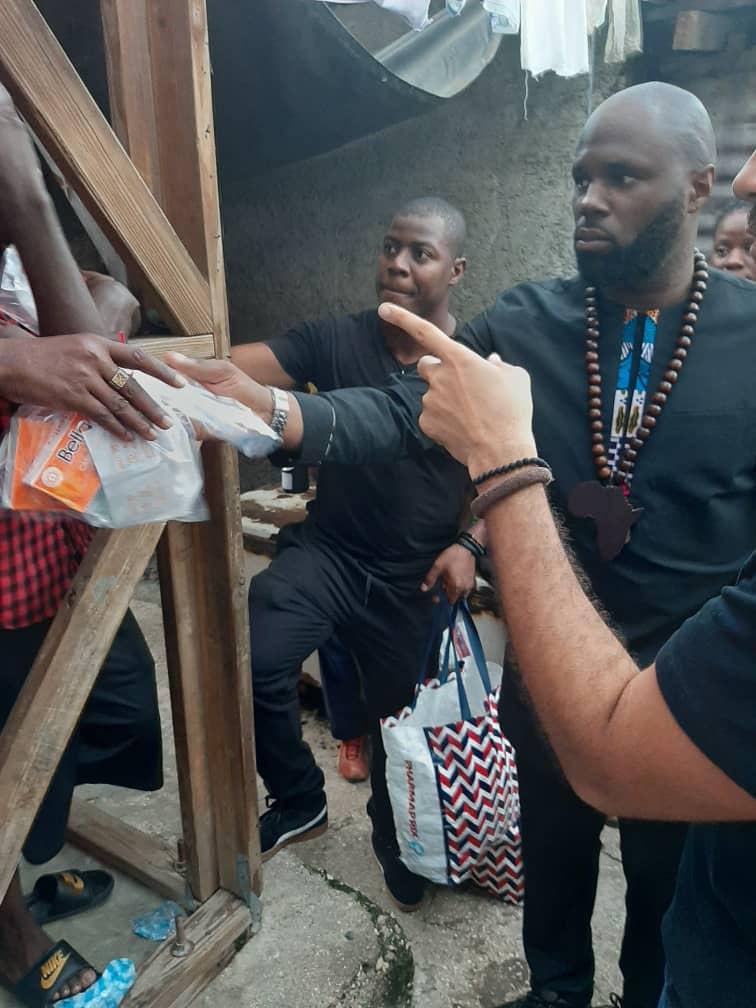 Kemi Seba distribuant un kit à un bénéficiaire