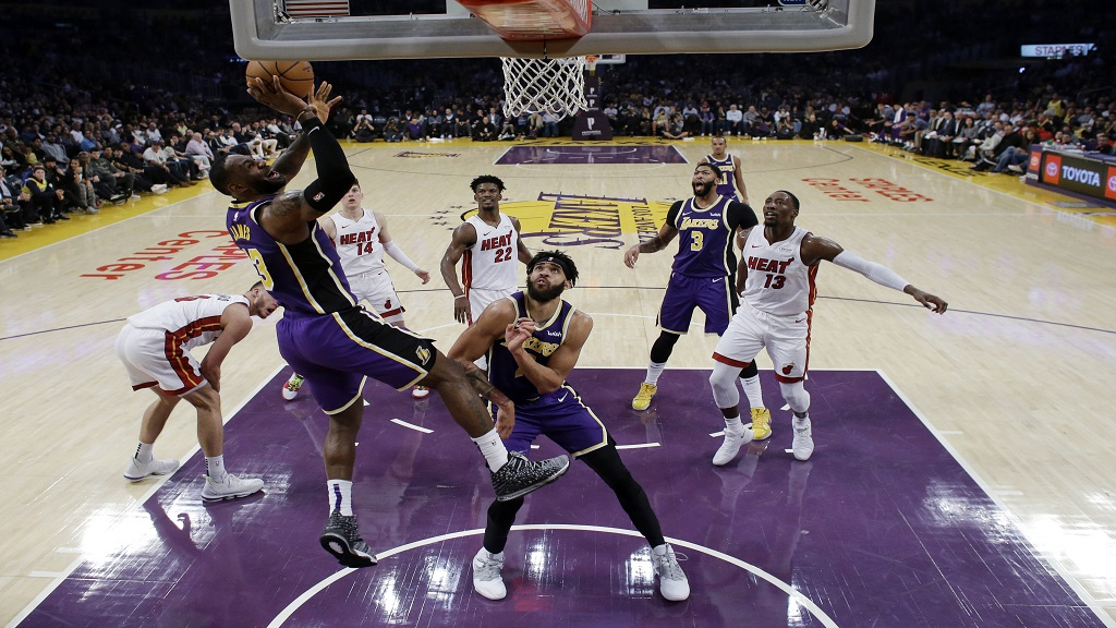 Los Angeles Lakers' LeBron James, left, drives to the basket against the Miami Heat during the second half of an NBA basketball game Friday, Nov. 8, 2019, in Los Angeles. (AP Photo/Marcio Jose Sanchez).