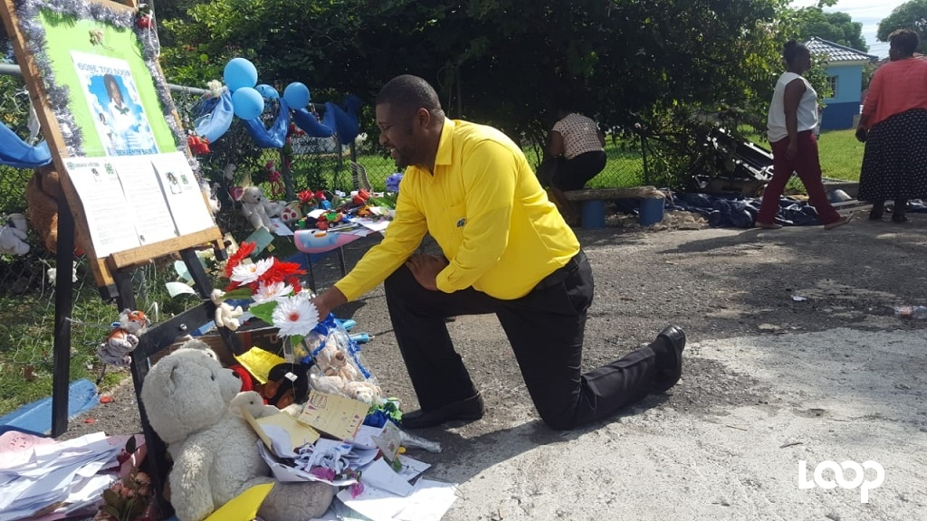 Sheldon Roberts, the principal of the Clan Carthy Primary School, is teary-eyed as he places flowers at a makeshift memorial for the late Benjamin Bair, who died in a freak accident on the school compound earlier this week. (Photos: Marlon Reid)