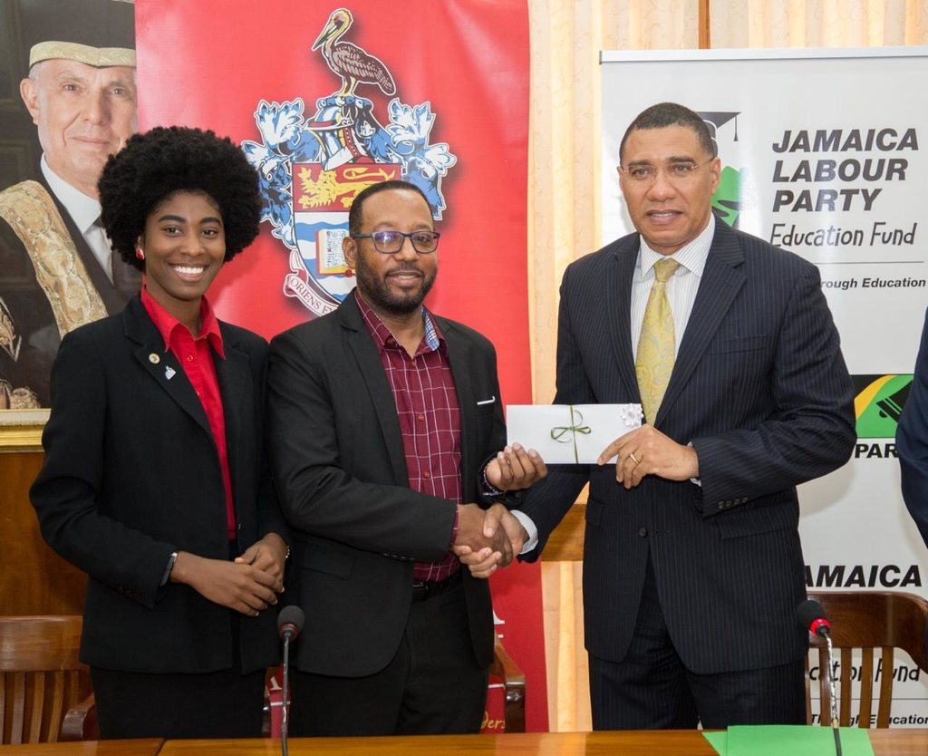 Prime Minister and Jamaica Labour Party Leader Andrew Holness (right) presents deputy principal of the University of the  West Indies, Mona, Professor Ian Boxhill with a cheque to assist students. Sharing in the moment is UWI Mona Guild President Christina Williams.
