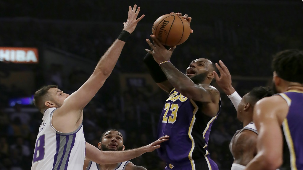 Los Angeles Lakers forward LeBron James, center, drives to the basket against Sacramento Kings forward Nemanja Bjelica, left, forward Richaun Holmes, right, and guard Cory Joseph (9) during the first half of an NBA basketball game in Los Angeles, Friday, Nov. 15, 2019. (AP Photo/Alex Gallardo).