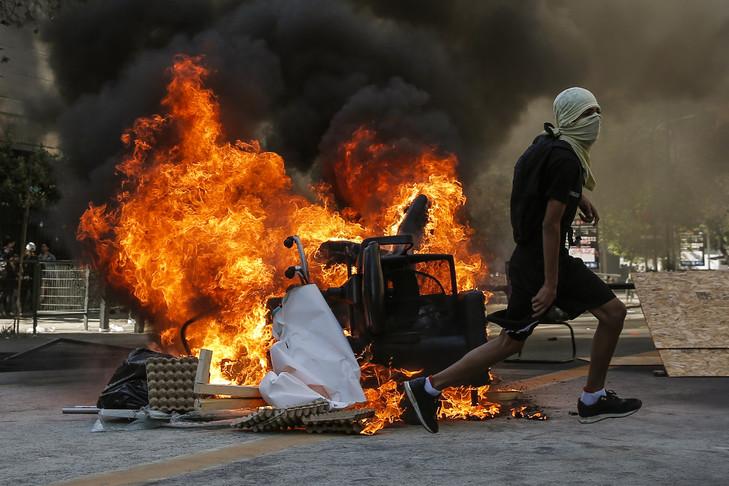 Un manifestant court devant une barricade enflammée, le 6 novembre 2019 à Santiago afp.com - JAVIER TORRES