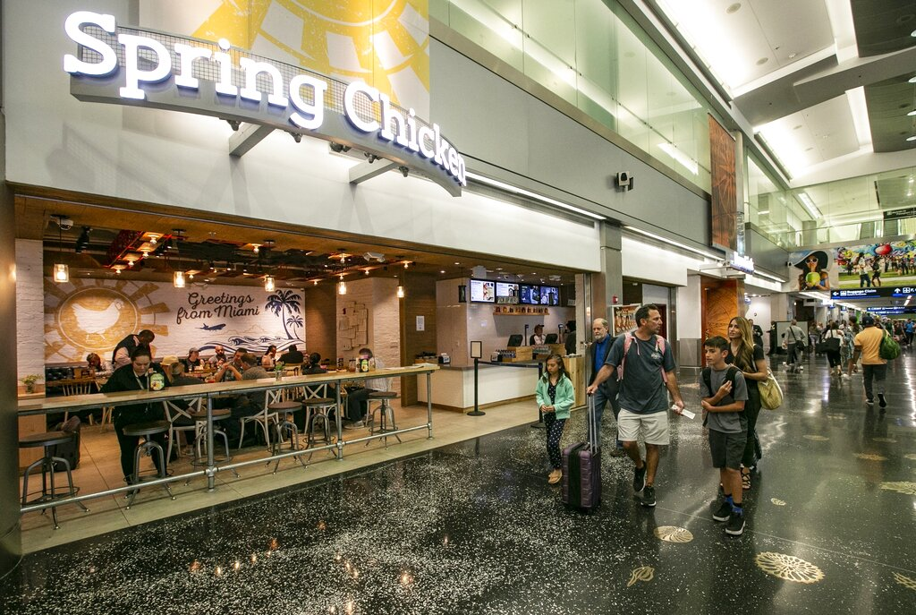 In this Thursday, April 4, 2019 photo, Travelers walk pass Spring Chicken Restaurant at Miami International Airport in Miami. Miami-Dade County is cracking down on automatic gratuities at restaurants at the airport. Restaurant workers say wages will plummet. (Al Diaz/Miami Herald via AP)