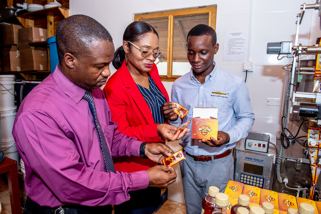 CEO of Las-Bee Producers Lascelles Smith (right) shows his Las-Bee Producers honey to to Scotiabank business manager Richard Nixon and branch manager Andrea Rhule-Hudson. Smith recently participated in the Scotia Vision Achiever Programme.