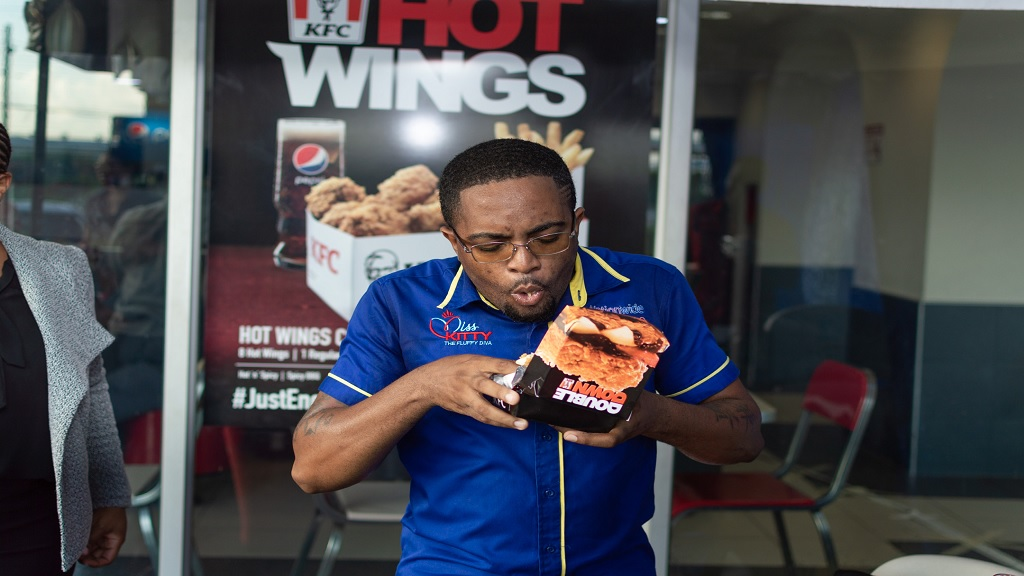 DJ Calico dives in and takes a big bite out of the spicy KFC Double Down sandwich at KFC Washington Boulevard.