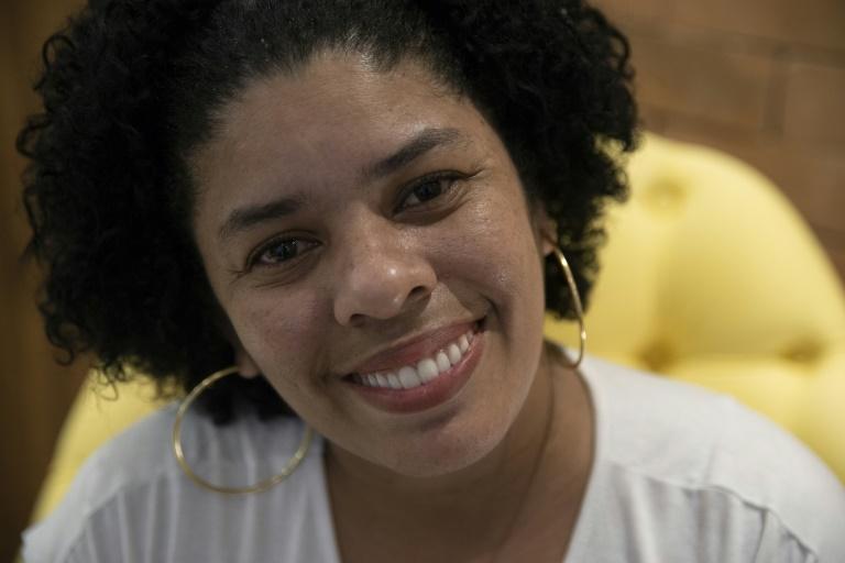 Ayant bénéficié de traitements de dentistes bénévoles pour récupérer une dentition détruite sous les coups de ses compagnons, Ana Claudia, 37 ans, sourit lors d'un entretien à l'AFP à Rio de Janeiro le 9 septembre 2019