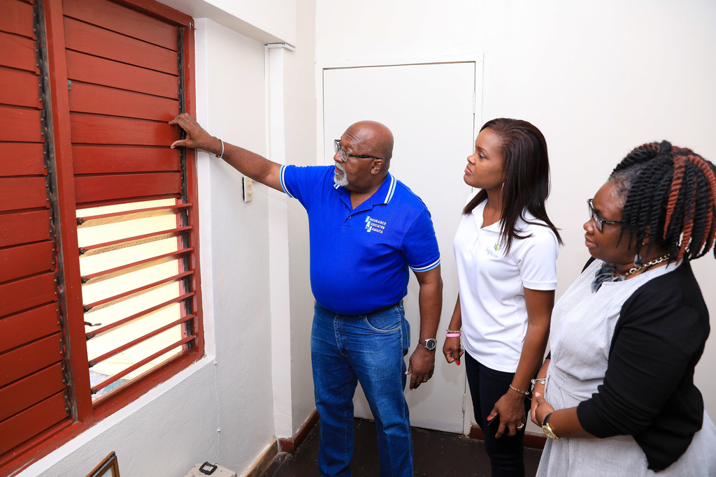 Chairman of the Best Care Foundation, Orville Johnson (left), shows Sagicor Life Financial Advisor, Bridgette Prendergast-Francis, windows updated during renovation of the Best Care Special Education School during a tour recently. The school is a past beneficiary of the Sagicor Sigma Corporate Run.