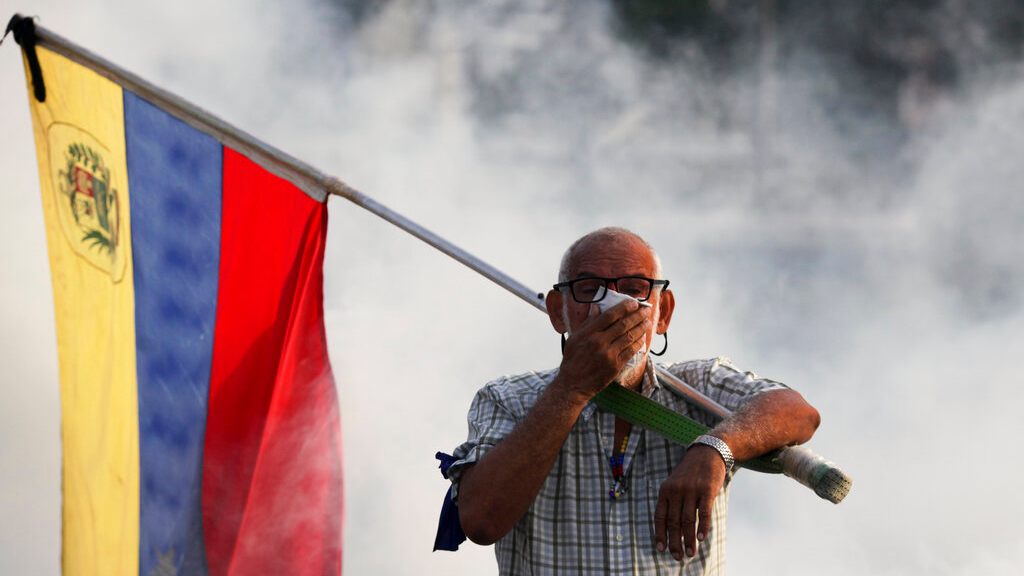 An opponent to Venezuelan President Nicolas Maduro carrying a Venezuelan flag covers his face amid tear gas fired by soldiers loyal to Maduro during an attempted military uprising to oust Maduro in Caracas, Venezuela, Tuesday, April 30, 2019.  (AP Photo/Boris Vergara)