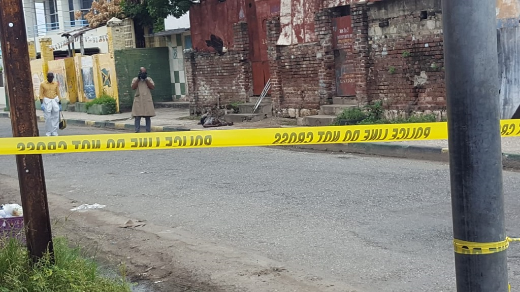 Police process the crime scene on North Street in downtown Kingston where an amputee was shot dead on Wednesday morning. (Photo: Marlon Reid)