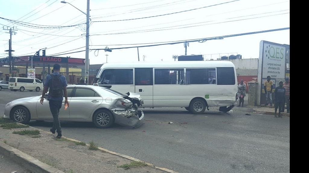 The bus and sedan pictured were among the vehicles damaged in a crash along Constant Spring Road on Friday.