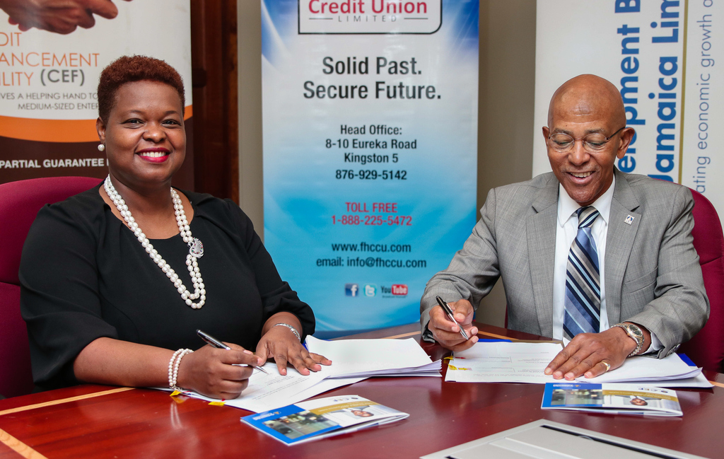 First Heritage Co-operative Credit Union (FHC) Chief Executive Officer Roxann Linton and Development Bank of Jamaica (DBJ) Managing Director Milverton Reynolds sign their respective copies of the new agreement between the two organisations at the DBJ office.