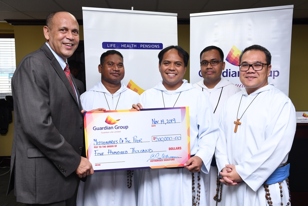Father Rodel D Tabanao (center) accepts a cheque of $500,00.00 from President of Guardian Life Limited, Eric Hosin (left) on behalf of the missionaries for the poor, with brothers Roger L Loremia (second left), James Kulluand and Father Lawrence L. Mendoza (right).
