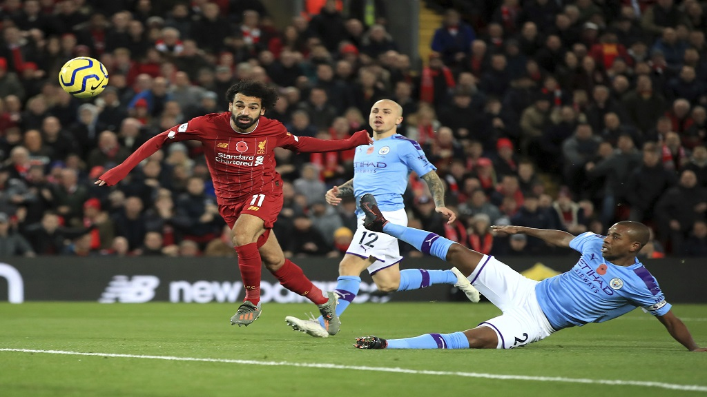Liverpool's Mohamed Salah, left, scores his side's second goal of the game during the English Premier League match at Anfield, Liverpool, England, Sunday November 10, 2019. (Peter Byrne/PA via AP)