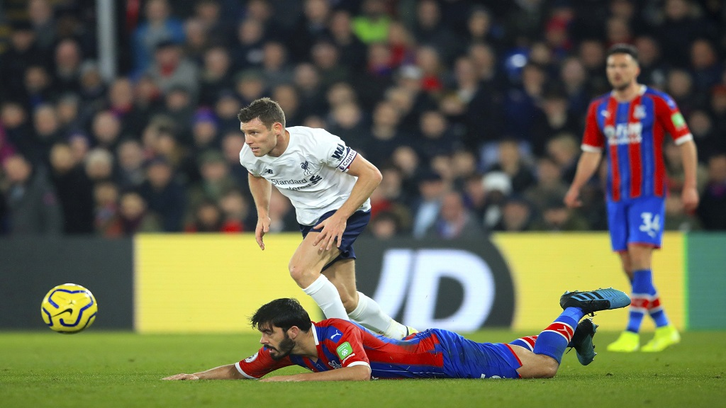 Liverpool's James Milner and Crystal Palace's James Tomkins battle for the ball during the English Premier League football match at Selhurst Park, London, Saturday, Nov. 23, 2019. (Adam Davy/PA via AP).