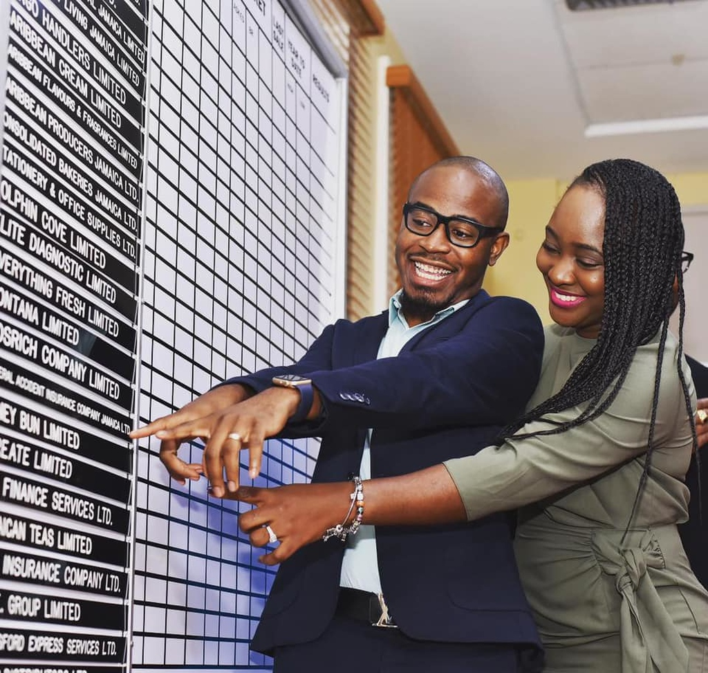 Tyrone Wilson (left), Founder & President of iCreate Institute and his wife Meisha-Gay Mattis Wilson point to the JSE trading board in celebration of the training institute's junior market listing.