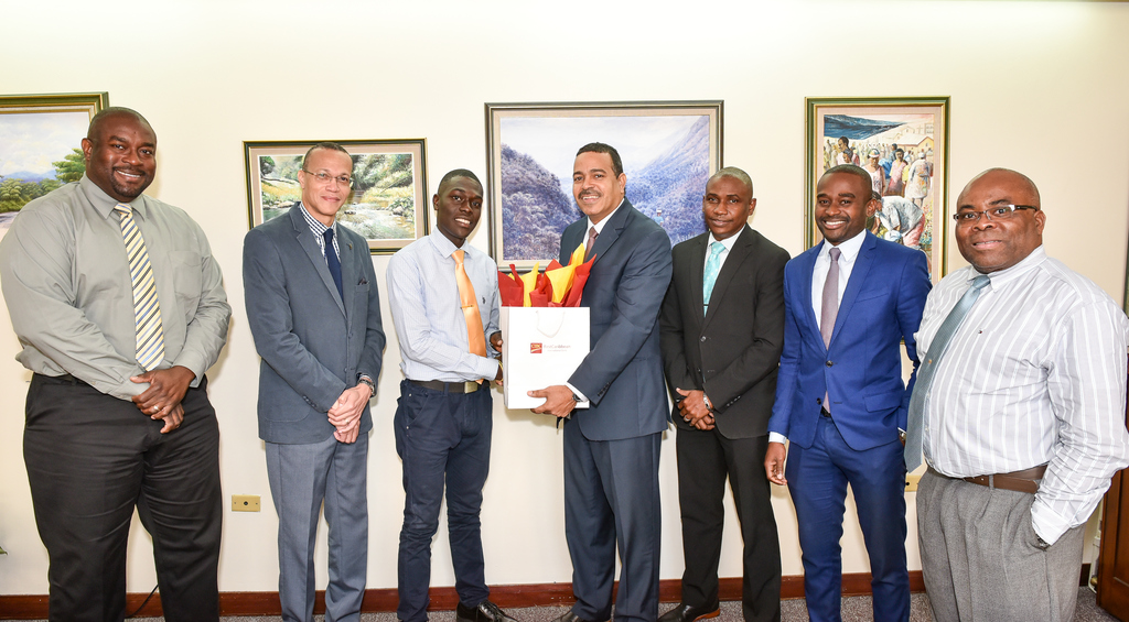 Nigel Holness (centre), Managing Director, CIBC FirstCaribbean International Bank presents a gift to Daniel Levy (3rd left), UWI student, who was guest of the bank on International Men's Day, November 19, 2019.  Sharing the moment were bank executives (l-r) Mark Lyons, Douglas Cupidon, Dwight Robinson, Jeffrey Brown, Corporate Manager and Royal Thorpe.