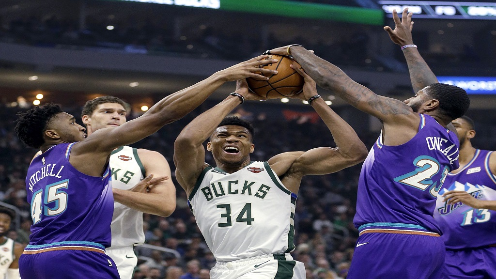 Milwaukee Bucks' Giannis Antetokounmpo (34) is fouled as he drives between Utah Jazz's Donovan Mitchell (45) and Royce O'Neale (23) during the first half of an NBA basketball game Monday, Nov. 25, 2019, in Milwaukee. (AP Photo/Aaron Gash).