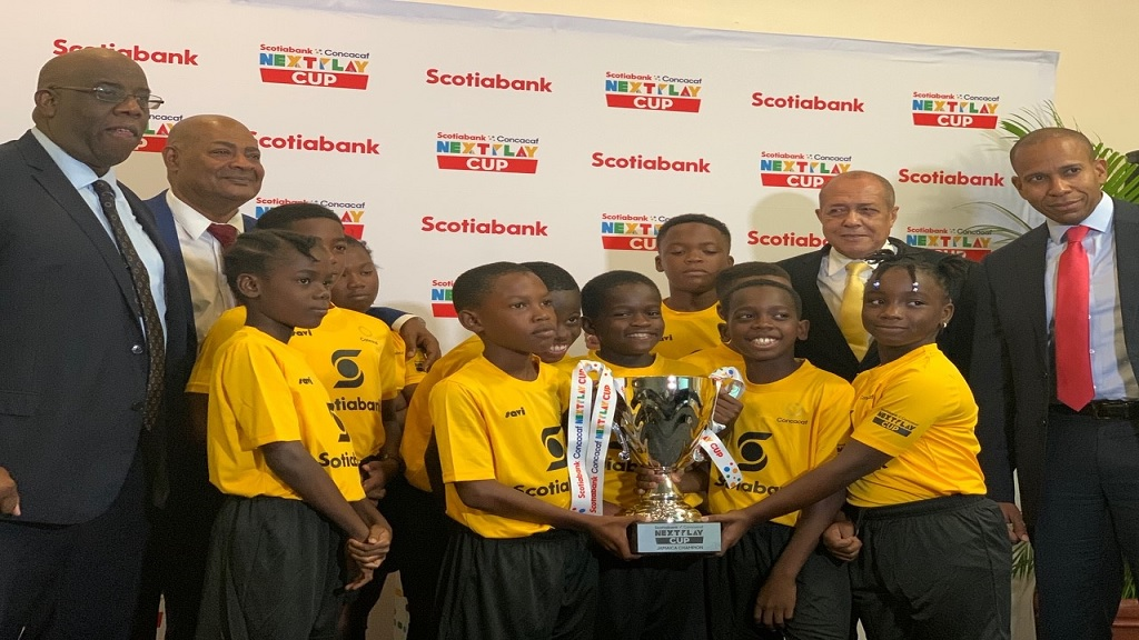 Last year's winners Holy Family Infant and Primary School with (standing from left) Concacaf Executive Howard McIntosh; JFF President Michael Ricketts; Sports Ministry Advisor Ali McNab and Scotia Group CEO David Noel.