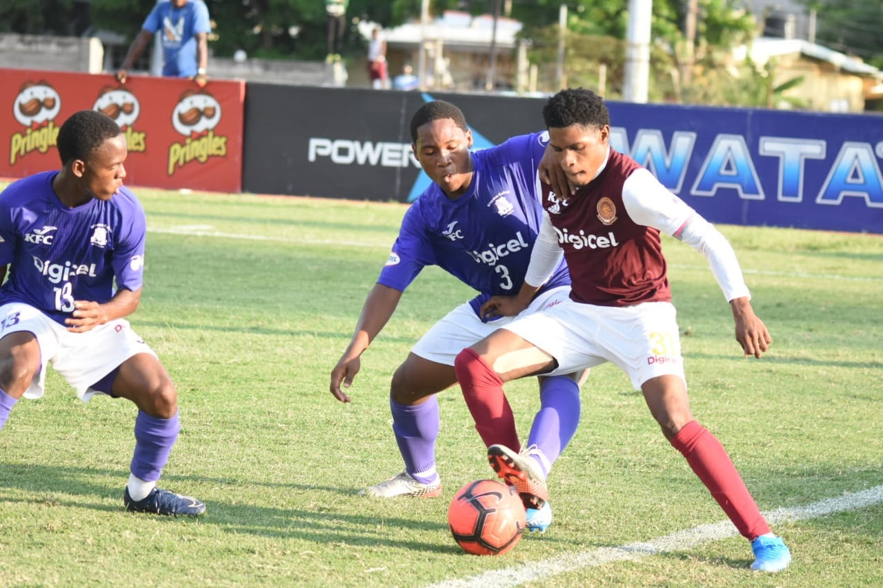 Kingston College's Dwane Atkinson (left) watches his teammate Khalifah Richards and Wolmer's Ronaldo Webster fight for possession during their Group G quarter-final round fixture of the 2019 ISSA/Digicel Manning Cup football competition at the Stadium East field on Tuesday, November 5. (PHOTOS: Marlon Reid).